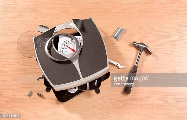 smashed bathroom scales with hammer - scale stock pictures, royalty-free photos & images