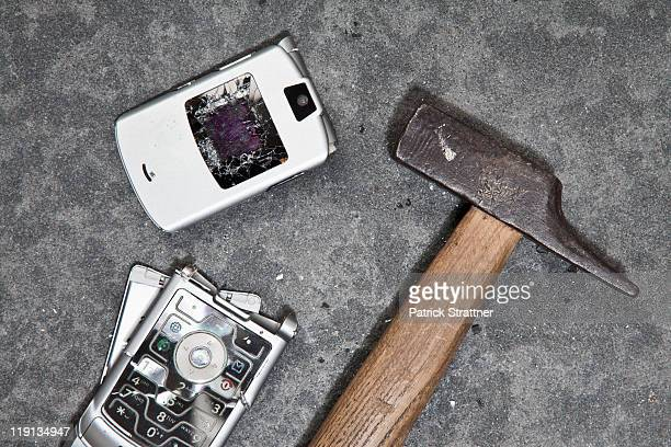 A smashed mobile phone and hammer