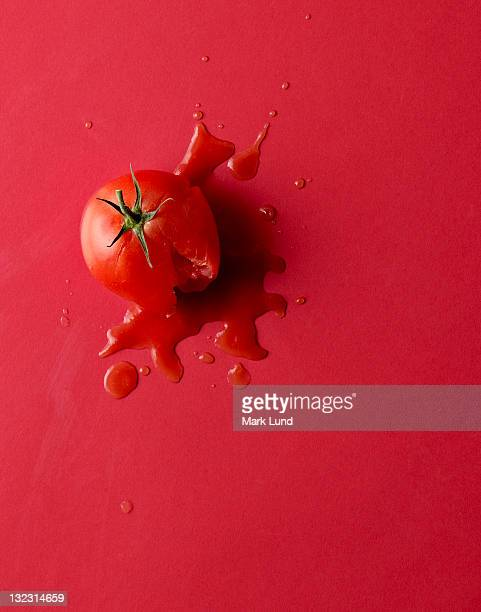 smashed tomato on red background. - crush foto e immagini stock