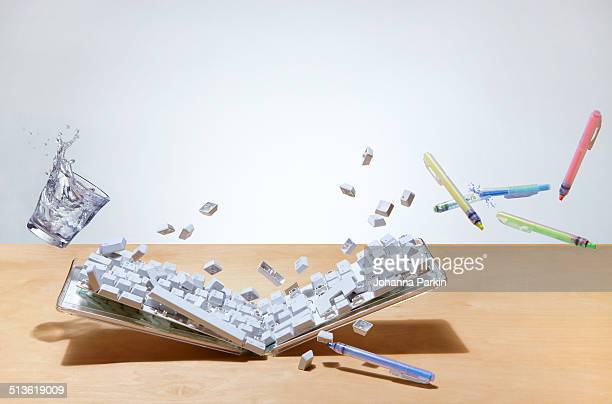 smashed up computer keyboard on office desk - demolishing photos stock photos and pictures