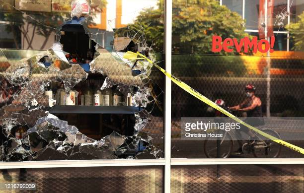 Smashed windows at a BevMo on La Cienega Boulevard catch a bicyclists attention on Sunday May 31 2020