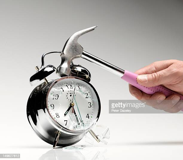 Smashing an alarm clock with a hammer