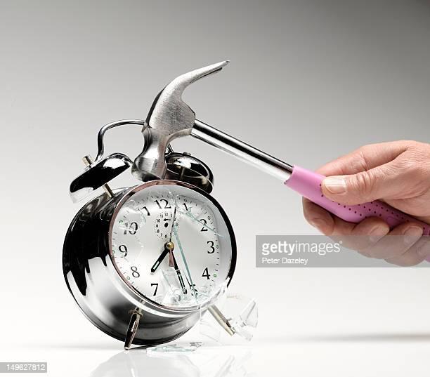 smashing an alarm clock with a hammer - rutina fotografías e imágenes de stock