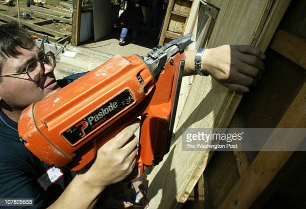 smchristmas Mark Gail_TWP Tom Grace uses a nail gun to attach a section of plywood to the outside of Jean Hardesty Pisgah's home being fixedup as...