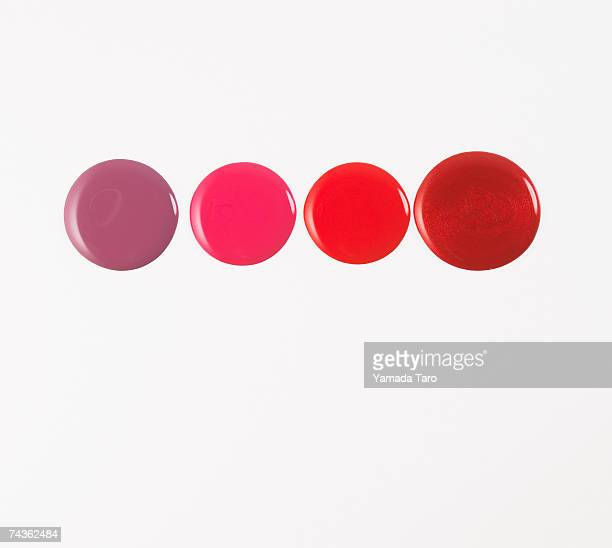 Smears of pink, red, brown, and purple lip gloss, close-up