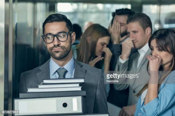 Homme d'affaires malodorante affectant ses collègues dans un ascenseur
