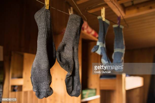 Smelly socks hang to dry in mountain hut after wet day of hiking, Kungsleden trail, Lapland, Sweden