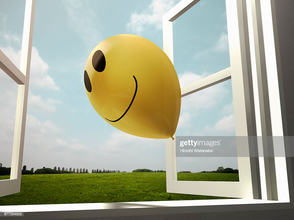 Smiley balloon  flies away to the sky : Stock Photo