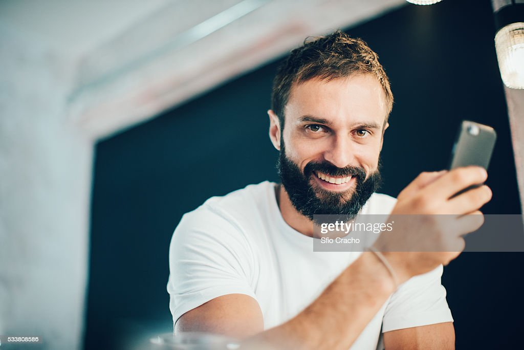 Smiley bearded man using smartphone : Foto stock