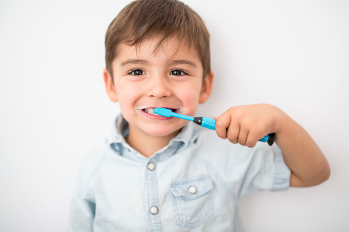 smiley boy cleans a teeth isolated on grey background 1075110002