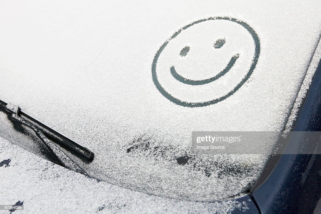 Smiley face in snow on car : Stock Photo