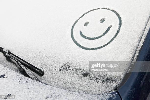 Smiley face in snow on car