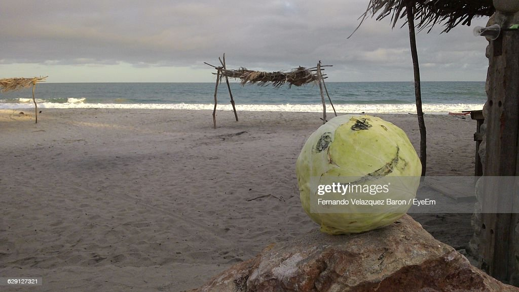 Smiley Face On Cabbage At Beach Against Cloudy Sky Stock Photo