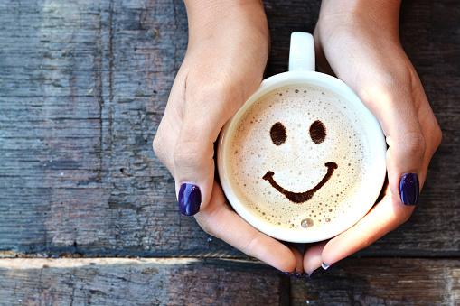 Smiley face on cappuccino foam, woman hands holding one cappuccino cup on wooden table 869326278