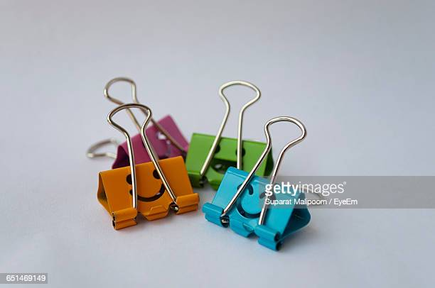 Smiley Face On Colorful Binder Clips On White Background