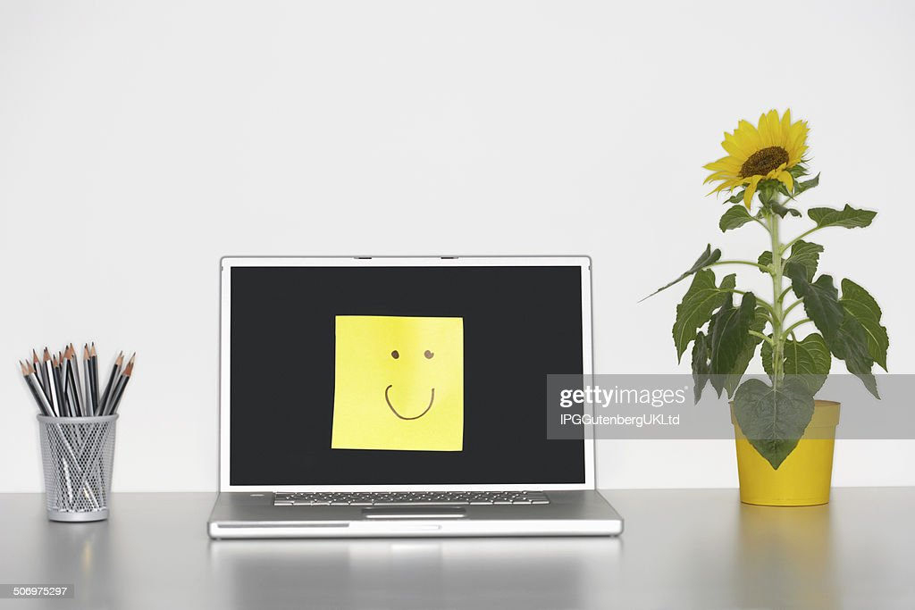 Smiley Face On Laptop Screen With Flowers And Pencils Stock Photo