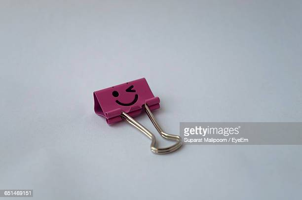 Smiley Face On Pink Binder Clip On White Background