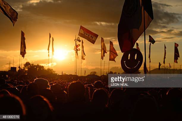 A smiley face sign is carried through the crowds as the sun sets on the first official day of the Glastonbury Festival of Music and Performing Arts...