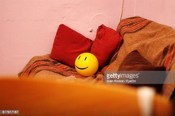 Smiley Face Stress Ball On Sofa At Home