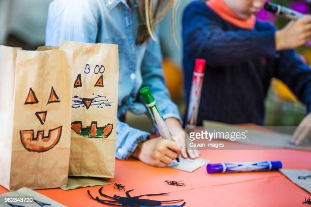 smiley faces on paper bags by siblings making art at table during halloween party - art and craft ストックフォトと画像