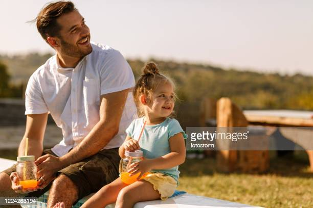 smiley father and daughter enjoying free time outdoors - june stock pictures, royalty-free photos & images