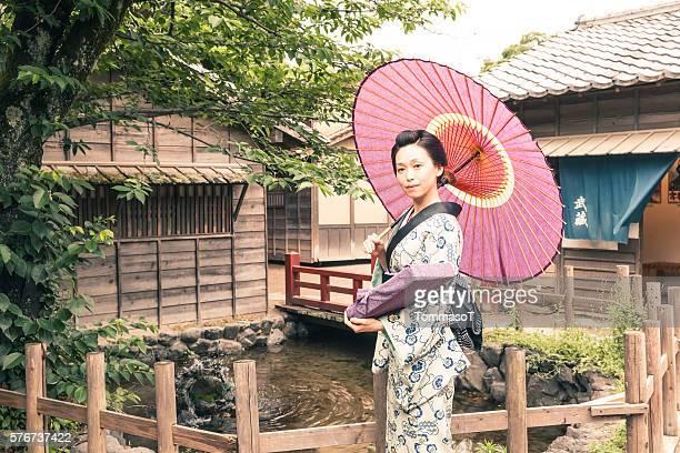 Smiley geisha with parasol in historic Kyoto