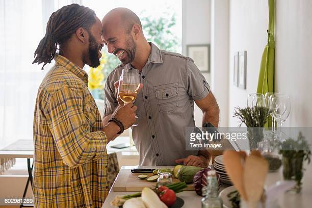 smiley homosexual couple drinking wine in kitchen - gay couple stock pictures, royalty-free photos & images