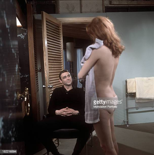 """Smiley Sean Connery looks at Luciana Paluzzi's wonderful figure during a break in the shooting of the bathtub scene from """"Thunderball"""" by Terence..."""