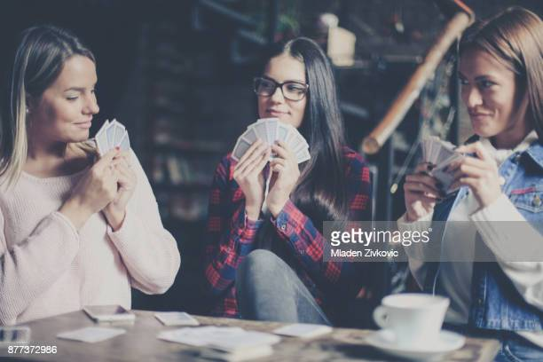 smiley three best friends in cafe playing together game cards. close up. - poker card game stock photos and pictures