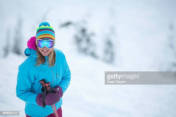 Smiley woman wearing skiwear on ski slope