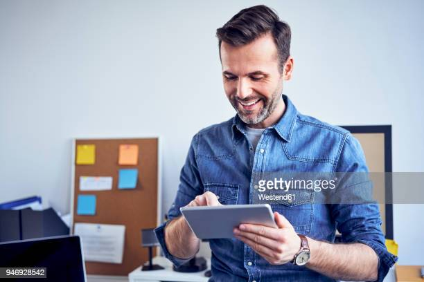 smilig man using tablet in office - one mid adult man only stock pictures, royalty-free photos & images