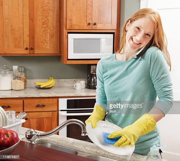 smiliing Junge Frau reden am Telefon während Abwaschen