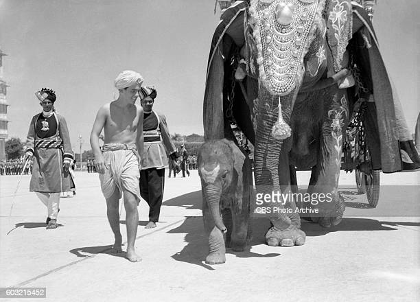 Smilin' Ed's Gang Nino Marcel star of Smilin Eds Gang parades in front of the palace of his host the Maharajah of Mysore with Tusker a baby elephant...