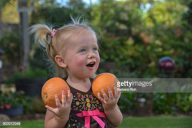 Smiling 1 1/2 year old girl holding grapefruits