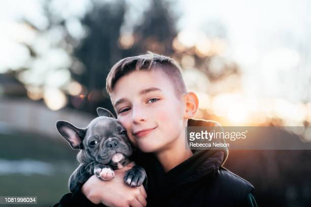 smiling 11-year-old boy holding French Bull dog closely