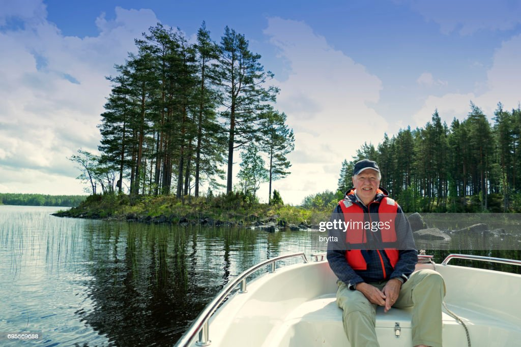 Smiling 73 years old senior wearing  a cap and a life jacket sitting in front of a motorboat sailing in Gastrikland,Sweden : Stock Photo