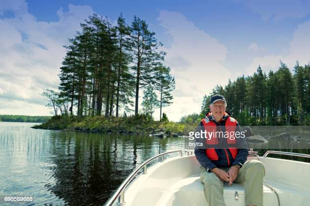 Smiling 73 years old senior wearing  a cap and a life jacket sitting in front of a motorboat sailing in Gastrikland,Sweden