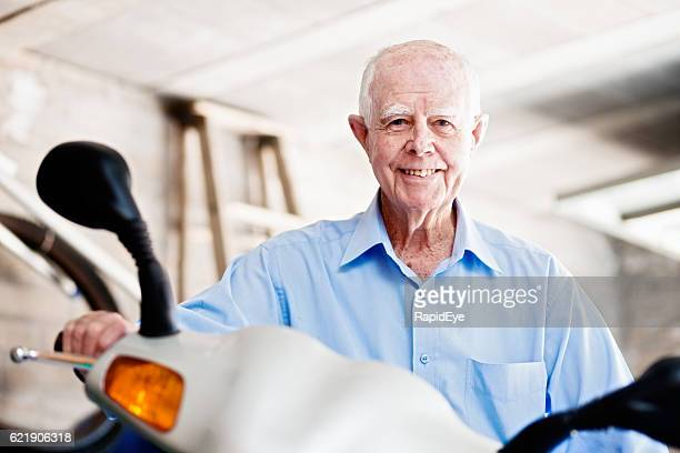 Smiling 90-year-old man sits on his motor scooter