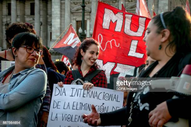 Smiling a protestor holds a sign calling for the elimination of violence against women Marching from the nation's iconic Congreso buildings to Plaza...