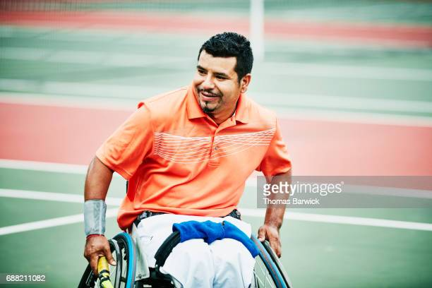 Smiling adaptive athlete moving across court during wheelchair tennis match