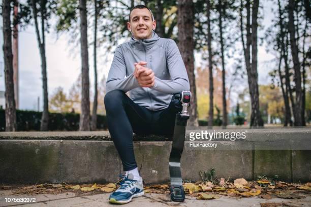 smiling adaptive athlete relaxing in the park - pessoas com deficiência imagens e fotografias de stock