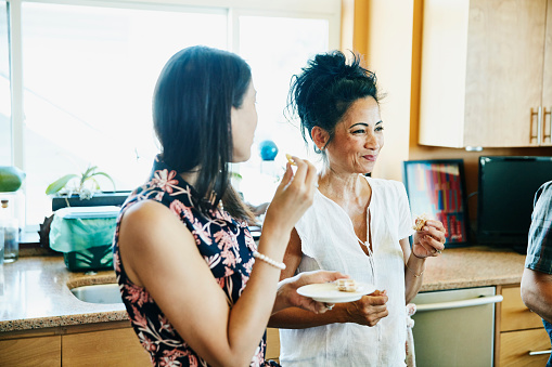 Smiling adult sisters hanging out in kitchen eating lunch - gettyimageskorea