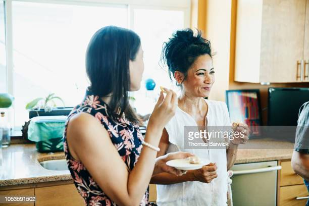 smiling adult sisters hanging out in kitchen eating lunch - family and happiness and diverse stock photos and pictures