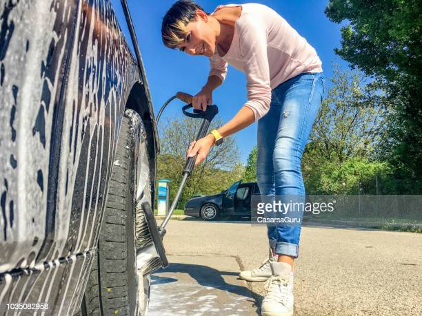 smiling adult woman brushing car wheels - car wash brush stock photos and pictures