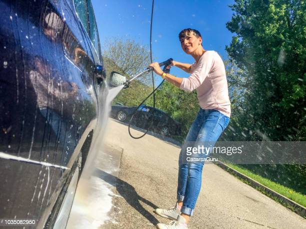 smiling adult woman cleaning her car in car wash - high pressure cleaning stock pictures, royalty-free photos & images
