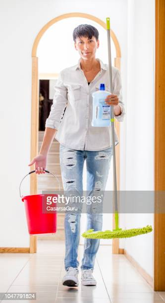 smiling adult woman holding cleaning equipment - daily bucket stock pictures, royalty-free photos & images