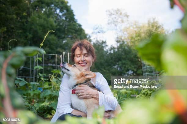 smiling adult woman hugging corgi dog outdoors in the garden - sourire à pleines dents photos et images de collection