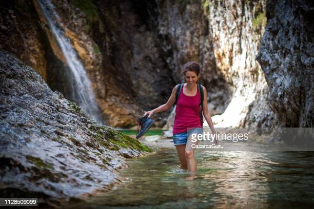 smiling adult woman walking in water and exploring a stream - mid adult women stock pictures, royalty-free photos & images