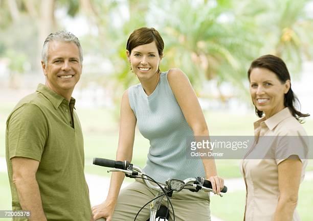 Smiling adults, one on bike