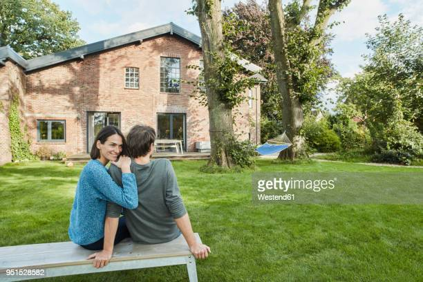 smiling affectionate couple sitting in garden of their home - wohnhaus stock-fotos und bilder